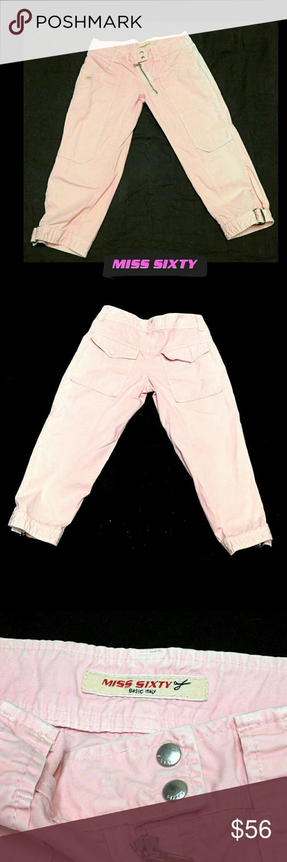 """MISS SIXTY PINK SLANT FRONT ZIP OPEN BUCKLE CROP MISS SIXTY PINK SLANT FRONT ZIP OPEN BUCKLE CROP PANTS Pre-Loved/EUC/Made in Italy SZ 28 These Are TOO COOL! UNIQUE! Double Snap Front w/Slant Zipper, Extra Front Knee Pockets,Back Flap Hidden Button Pockets CROP Has Slit to Tighten by Attached Buckle Wide Belt Loops Approx Meas;       *   Waist   15""""    *   Inseam    21""""    *   Rise   7 1/2""""    *   Slit L.   7""""    *   Leg Opening.   7"""" Pls See All Pics. Ask ? If Not Sure Miss Sixty Jeans…"""