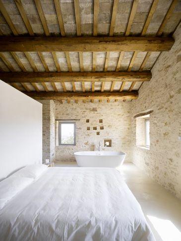 Rustic and minimal bedroom. stone walls, exposed beams, freestanding basin bathtub.