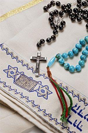 Sichtbare Zeichen religiöser Identität – exemplarisch ein christlicher Rosenkranz, eine islamische Gebetskette, die Misbaha genannt wird, und ein jüdischer Gebetsschal, der Tallit heißt.