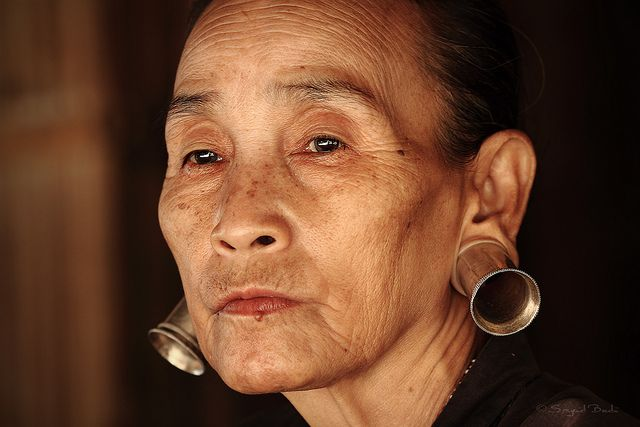 A Padaung lady with stretched ear lobes by  DocBudie, via Flickr