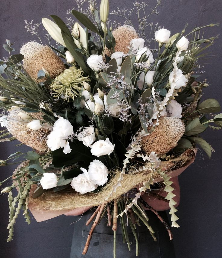 Banksias, foliage and lissianthus arrangement to make a statement.