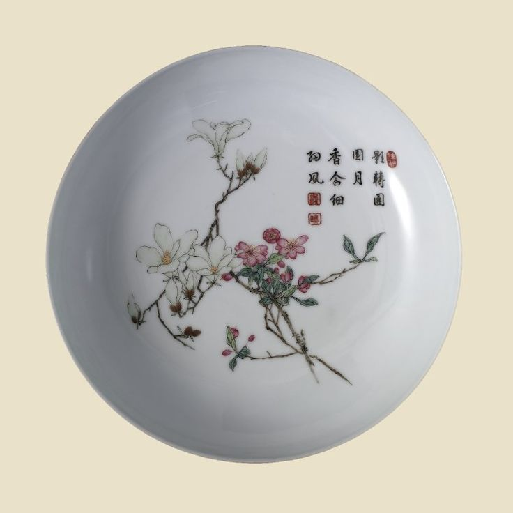 Saucer-shaped fine thin white porcelain dish. Decorated 'Gu Yue' style in 'famille rose' enamels. Inside is a delicately drawn design of blossoming magnolia and peach spray together with a poetical inscription with three seals in red enamel. Pair with PDF 856.