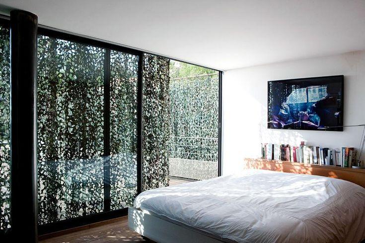 VILLA LE GOFF: LA CAMERA DA LETTO Le grandi vetrate sono schermate, dove occorre, da una tenda mimetica militare con funzione di frangisole