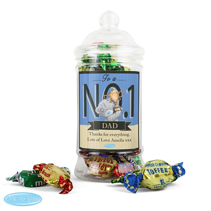 "This Me to You toffee jar is a cute way to let him know that he's your ""number one"".  Personalise with a role up to 10 characters within the banner, eg Dad, Granddad, Godfather and a message below of 2 lines up to 30 characters per line.   The text ""To a No 1"" is a fixed part of the design.  Personalisation within the banner will appear in UPPERCASE. All other text will appear as entered and is case sensitive.   Please refrain from using special characters as this may impair the quality of…"