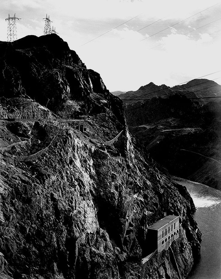 """Boulder Dam, 1941,"" vertical of side of cliff with transmission lines above, river to left."