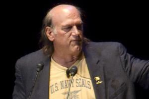 """Jesse Ventura speaking at a podium. The former governor of Minnesota contended that his reputation had been """"destroyed"""" by fabrications in a book by the late Chris Kyle, choking off lucrative job offers in the entertainment industry, while defense attorneys in the federal defamation trial introduced evidence to suggest Ventura had ruined his own credibility with inflammatory statements over the past decade."""