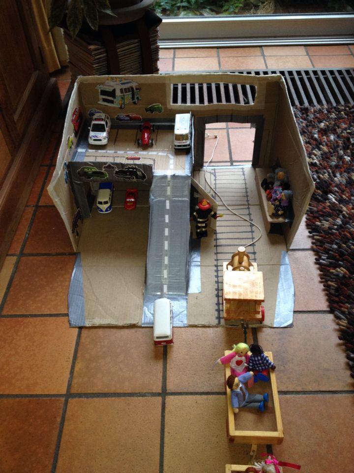 Al die dure ontwikkelingsmaterialen... Wat als je geen budget hebt? Dan maak je gewoon iets zelf (of je laat het de kinderen maken)! Bijvoorbeeld deze garage, leuk in het thema verkeer.
