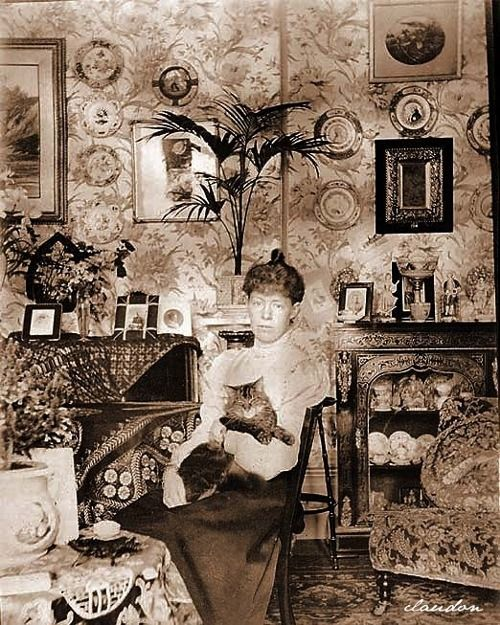 Victorian/Edwardian woman and  her cat. Beautiful living room, parlor.