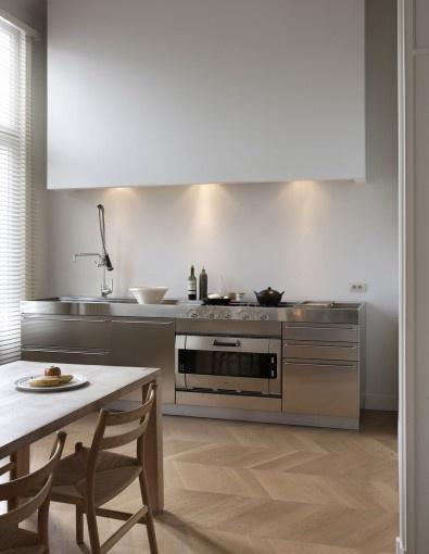 Moderne rvs keukenfronten en strakke #schouw ombouw met klassieke #hongaarsepunt houten vloer of parket