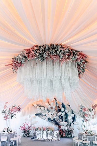 This surreal wedding reception of grays, pinks, and metallics transports one to another world, with modern, almost futuristic décor and one dramatic ceiling chandelier.