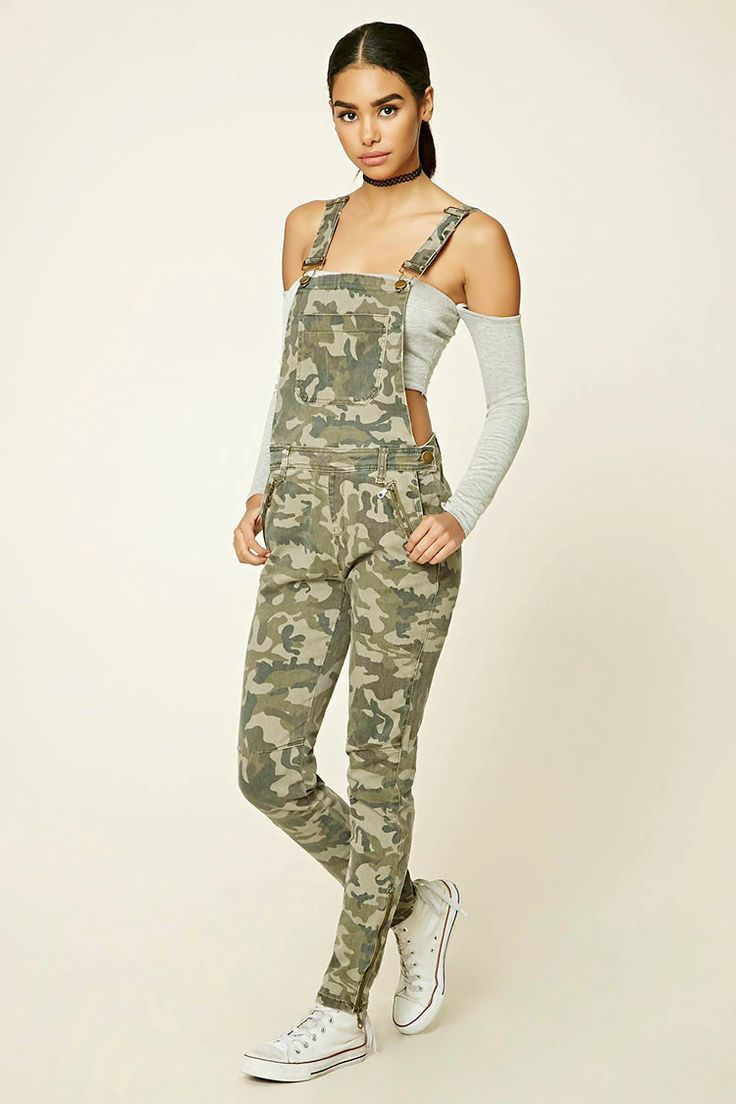 A pair of knit overalls featuring a camo print, a three-pocket construction, adjustable straps with slide-lock closure, mock zipper pockets, a mock back flap pocket, ankle zippers, and button sides.