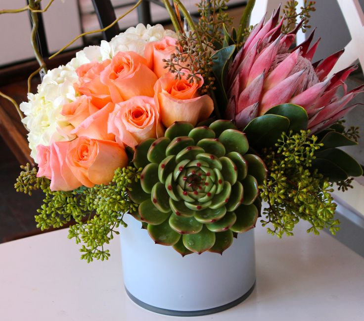 $149.99 Arrangement. Roses, hydrangea, succulent, King Protea and seeded eucalyptus arranged in a white cylinder vase.