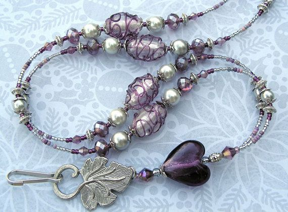 Handmade by yours truly!  Excellent gift for nurses, teachers, airline workers - basically anybody with a job in public relations.  Very elegant lanyard! One luscious purple heart made of lampwork glass, elegant light grey glass beads decorated with delicate purple scrolls, glass pearls and assorted metal & seed beads. Utterly elegant. Distance from neck to bottom of stunning, leaf-shaped ID - hanging ring is 19 inches. Reaches below chest area, ideal size.  I used stainless steel beading...