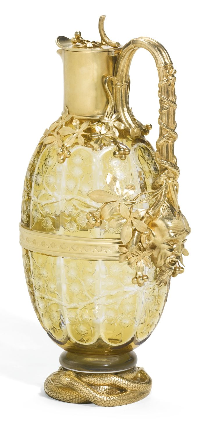 A Fabergé cut and coloured glass decanter with silver-gilt mounts, Moscow, circa 1890, in Far Eastern taste, the yellow glass body of oval section and cut with branches of chrysanthemum, divided by a central band chased with stylised lotus, the plain collar issuing the handle formed as a branch of clematis and terminating in a Chinese mask of an old man with plaited hair, the base cast as a coiling snake.