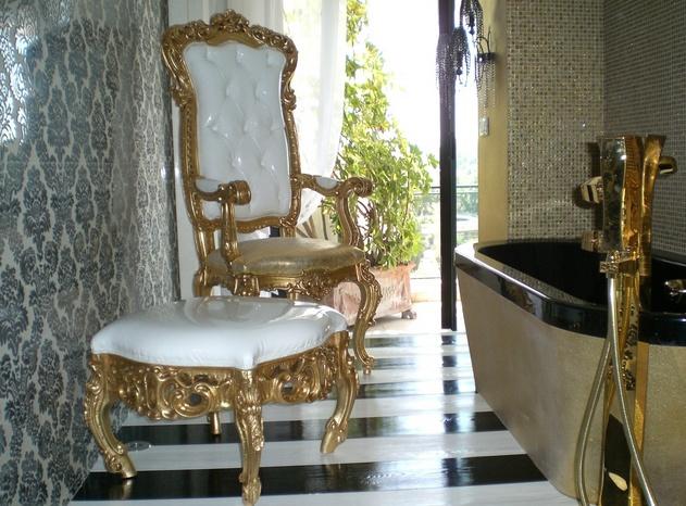 Luxe, hoge rugleuning stoel en bijpassende hocker in Hotel Badkamer.