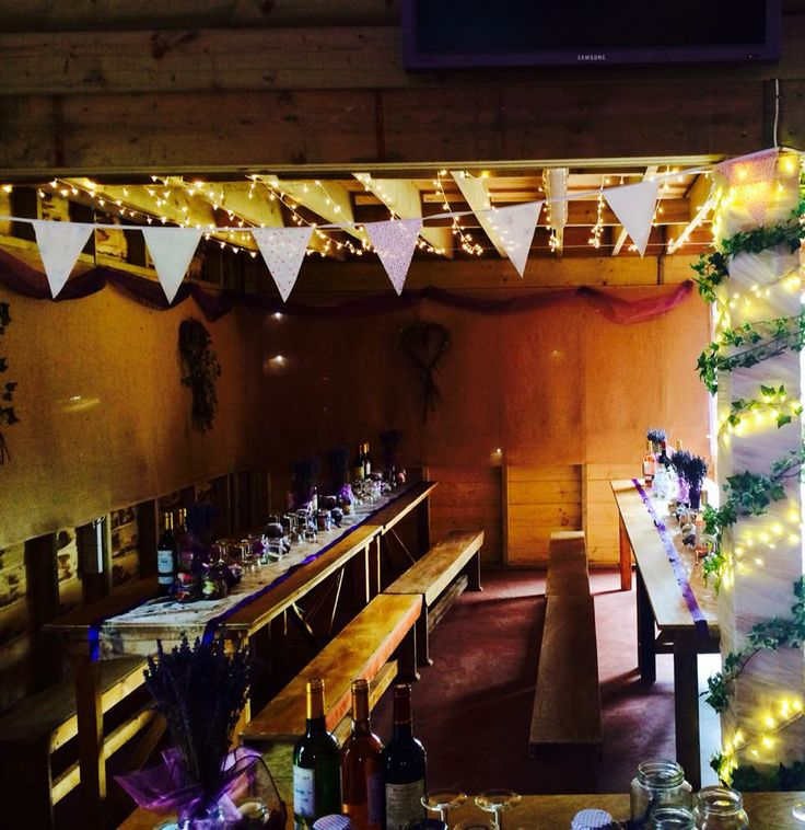 wedding decorations, bunting, organza table runners, lavender in old jars and fairy lights in an old barn setting.