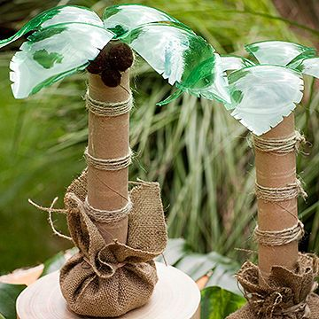 """Top the buffet table with palm trees made from recycled green soda bottles, paper towel tubes, and twine.                 What You'll Need: 8-oz. green plastic soda bottle, scissors, 8"""" square of burlap, paper-towel tube, rubber band, twine, 2 cups dried beans, hot-glue gun, medium brown pom-poms                 Make it: Remove the label on the soda bottle and cut off and discard the bottom fourth. Cut four evenly spaced slits down toward the neck of the bottle. Bend back the remaining…"""
