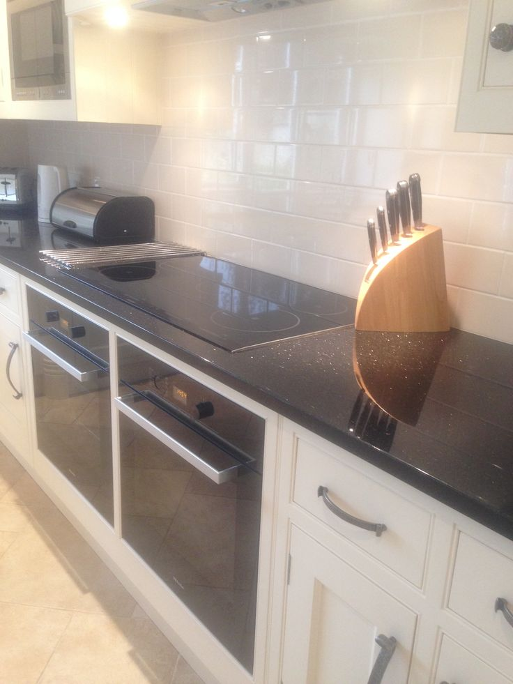Lovely clean kitchen with cream subway tiles, black granite top, mielle ovens and oak units painted white