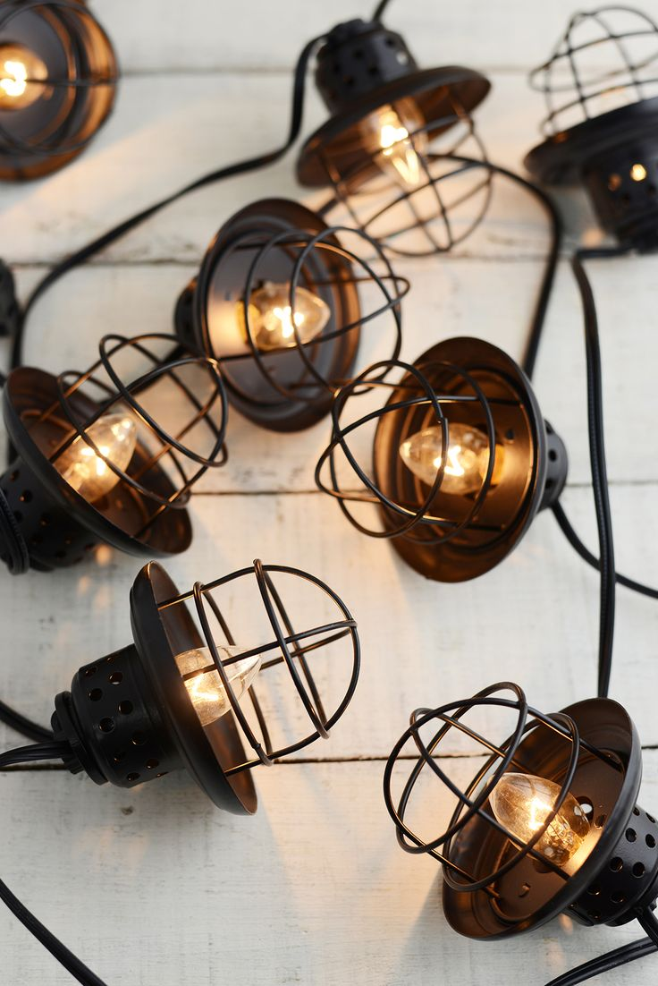 "Metal Lantern String Lights. 10 lights enclosed in black metal caged lanterns. Can connect three together to create a grand display above an outdoor wedding dance floor. Indoors or outdoors. Strand has a lighted length of 9' with 6"" of cord at either end. Lanterns 3.5"" tall."