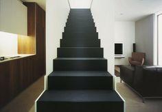 """: A escada emprega um compensado altamente resistente, revestido de filme plástico preto antiderrapante (Diamond Ply, da Finnforest). Embaixo dela, há um armário e um pequeno lavabo. A reforma desta casa em Londres, comandada pelo arquiteto Cris Godfrey, da Scappe Architects, mudou a escada de lugar. """"Nós a usamos para criar ordem, separação e conexão entre a sala, a cozinha, o quarto e o banheiro"""", afirma."""