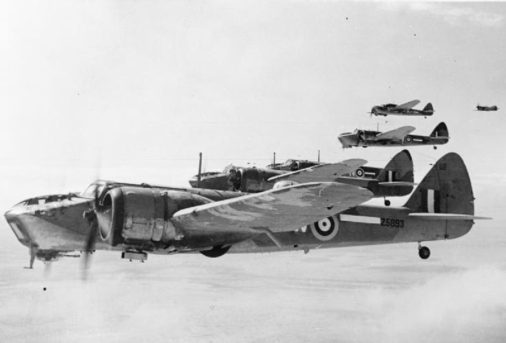 A formation of five Blenheim Mark IVs (Z5893 'W' nearest) of No. 14 Squadron RAF in flight over the Western Desert. A Curtiss Kittyhawk, one of the escorting fighters, can be seen on the far right.