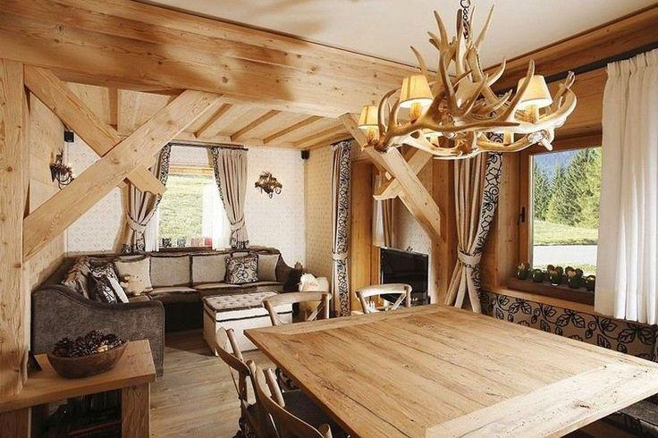 déco style campagne dans l'intérieur à aire ouverte avec un revêtement mural et de sol en bois, canapé d'angle, table en bois clair et lustre en cornes de cerf