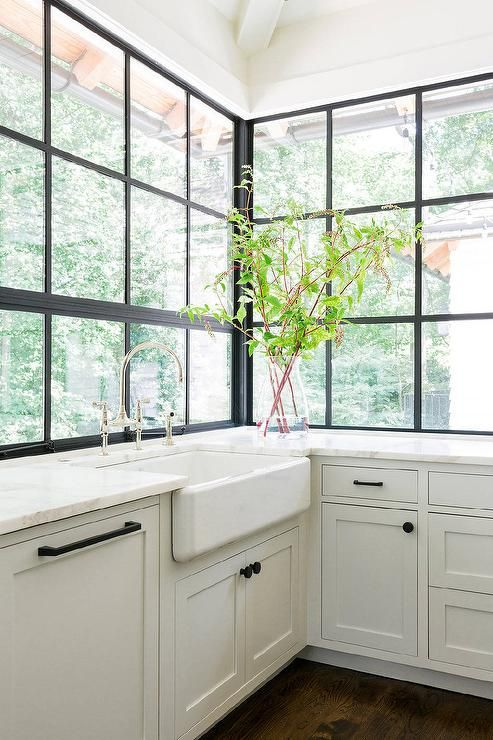 A farmhouse sink and deck-mount gooseneck faucet stands under black framed factory windows surrounded by white shaker cabinets adorned with oil-rubbed bronze hardware and honed white marble countertops.