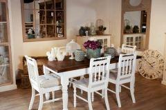 Stół i krzesła stanowiące komplet mebli do salonu bądź jadalni. Prostokątny stół z białymi nogami i kontrastującym blatem w naturalny kolorze drewna. Ozdobne białe krzesła drewniane, które można wyposażyć w poduszki do siedzenia.