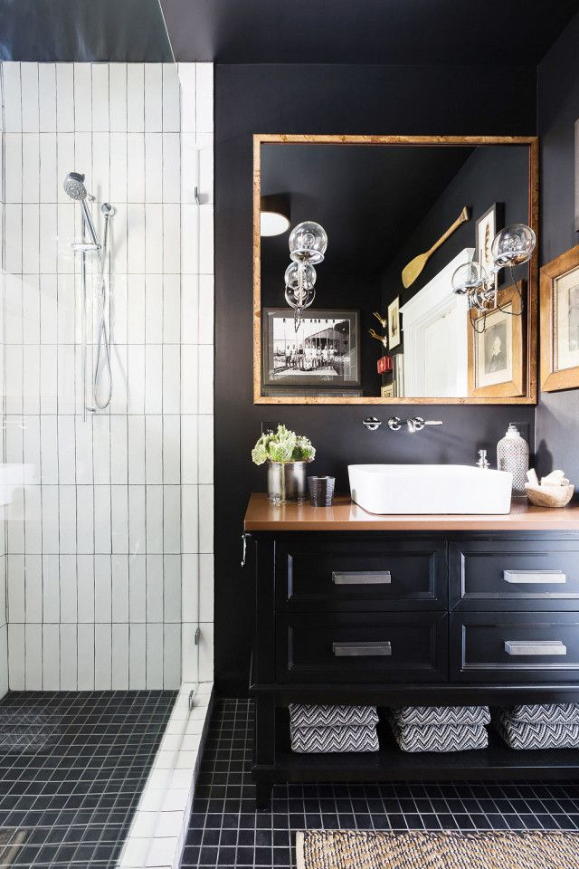 Bathroom with black walls, a white tiled shower, a traditional black vanity and a bronze mirror