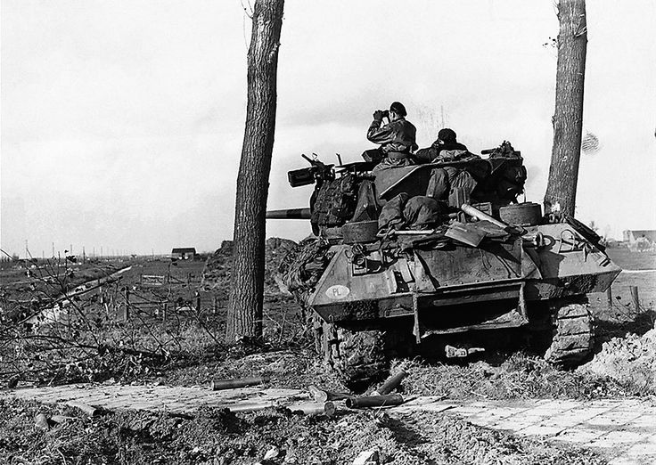 """Polish front line tank troops in the Battle of the Lower Rhine. Crew of a 17pdr SP Achilles Tank Destroyer the British variant of the American M10 tank destroyer armed with the powerful British Ordnance QF 17 pounder anti-tank gun in place of the standard 3"""" (76.2 mm) Gun M7. look for enemy troop movement. Empty shell cases lie on the ground beside them. Location between Terheijden and Oosterhout in the Netherlands 