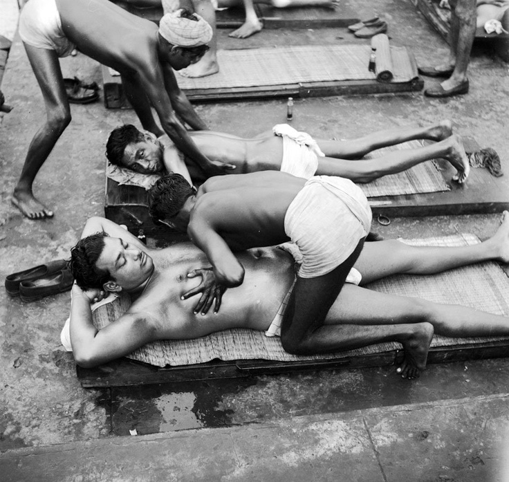 Masseurs+giving+a+chest+massage+to+bathers+after+their+morning+dip+-+India+c1950's