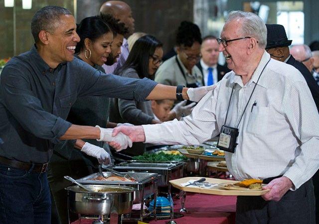 Barack Obama serve veteranos das Forças Armadas ao lado de Michelle e Sasha (Foto: Getty Images)