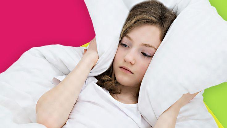 Ein Mädchen liegt im Bett und hält sich von beiden Seiten das Kopfkissen an die Ohren.