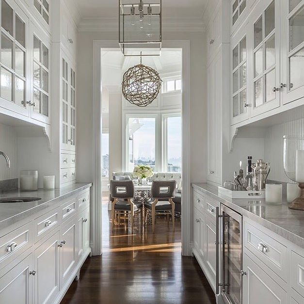 a traditional butlers pantry is tucked behind the main kitchen of this glamorous california home by