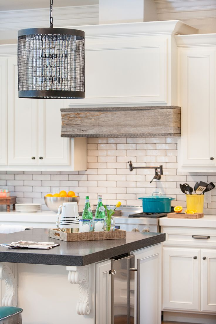 Unique, range hood wrapped with reclaimed barn wood. Room by Kendall Simmons Interiors.