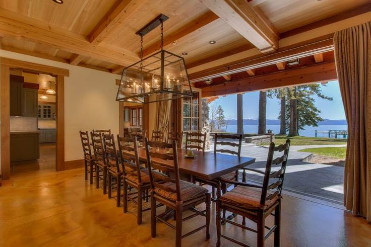 Sliding wall opens up the dining room to the lakefront patio at Laughing Waters - a Tahoe City lakefront Vacation Rental | Tahoe Luxury Properties
