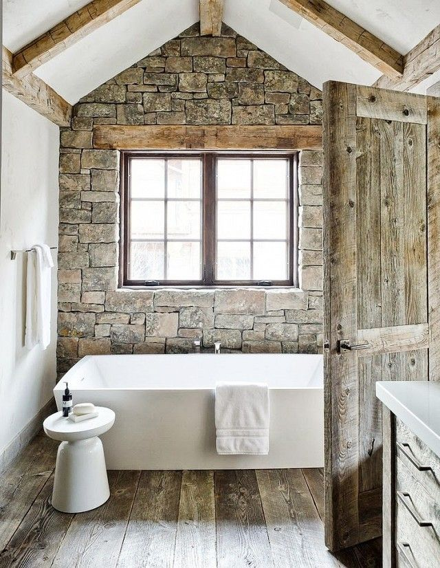 Ski chalet bathroom with wood floor, brick walls, and a floating tub