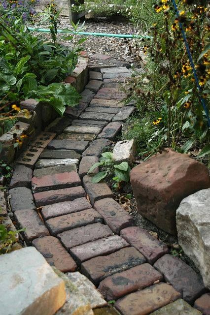 Narrow garden path of used paver brick...