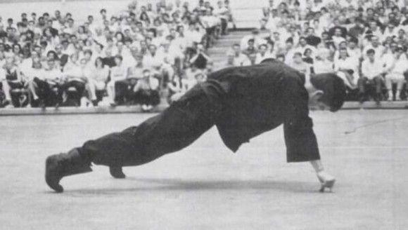 Bruce Lee realizando flexiones con una mano y con sólo el dedo indice y pulgar de apoyo.