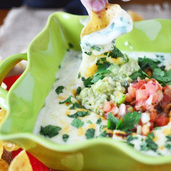 Chili's Copycat White Spinach Queso is rich and creamy, packed with spinach, baked to perfection, and topped with guacamole and pico!