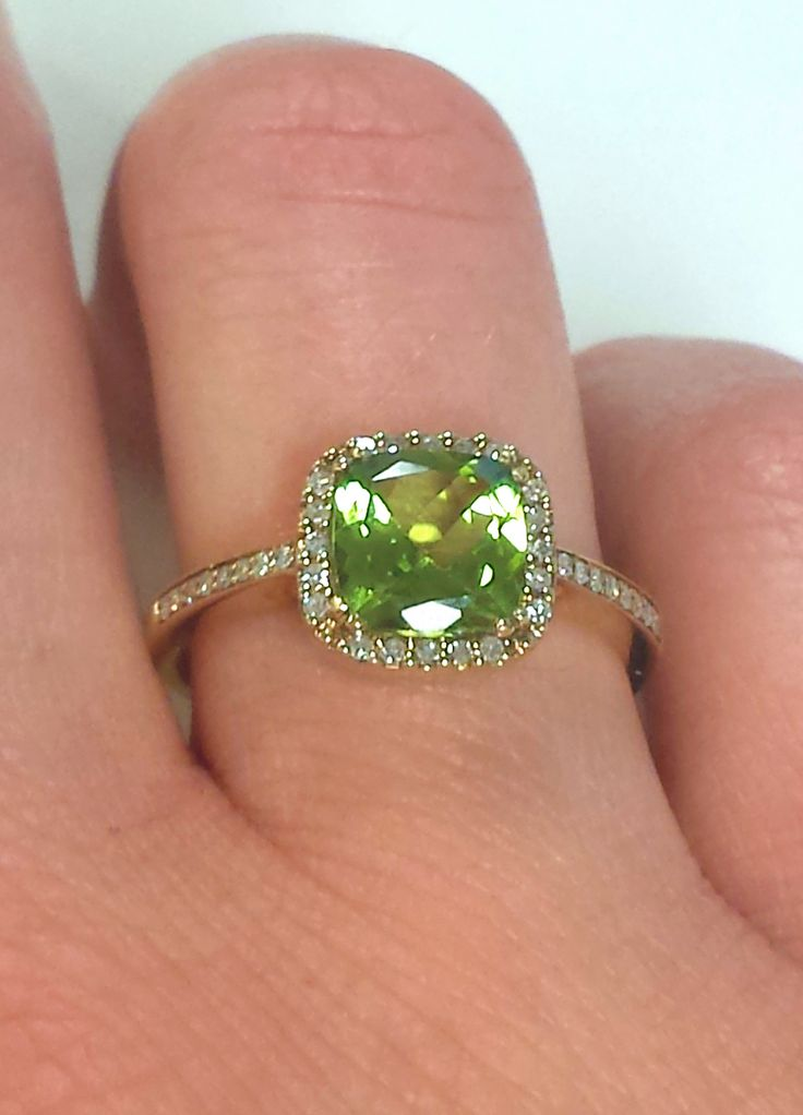 Get ready for spring with this cushion cut green peridot ring with a diamond halo and yellow gold band.