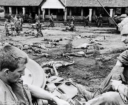 Bodies of dead North Vietnamese Army (NVA) troops who attempted to hold the rubber plantation village are laid out in an open area so they can be checked for documents before burial. In the foreground are 4719590 Trooper (Tpr) Ken Wilson (left) and 5715768 Tpr Laurie Sullivan (right) of B Squadron, 1st Armoured Regiment, Royal Australian Armoured Corps, discussing the breech mechanism of a .30 machine gun mounted on Centurion tank callsign 24C which took part in the battle.