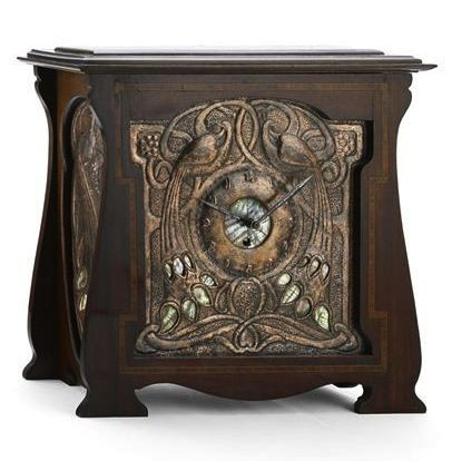 GLASGOW SCHOOL MANTEL CLOCK, CIRCA 1910 the dial of repousse-decorated copper, inlaid with mother of pearl with similarly decorated side panels, the whole enclosed within mahogany case with satinwood banding 42cm wide, 40cm high
