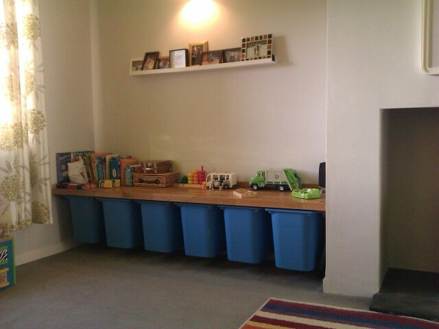 Lounge toy storage using Ikea toy storage boxes to underside of built in play surface / shelf.