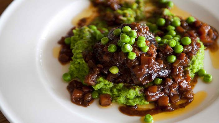 Braised beef cheeks in barbera (guanciale di manzo al barbera) | In this hearty Italian dish, chef Stefano Manfredi cooks cinnamon and bay leave-spiced beef cheeks in barbera, an Italian red wine. Serve atop a bed of warm pea purée, scatter with whole peas and drizzle with olive oil.