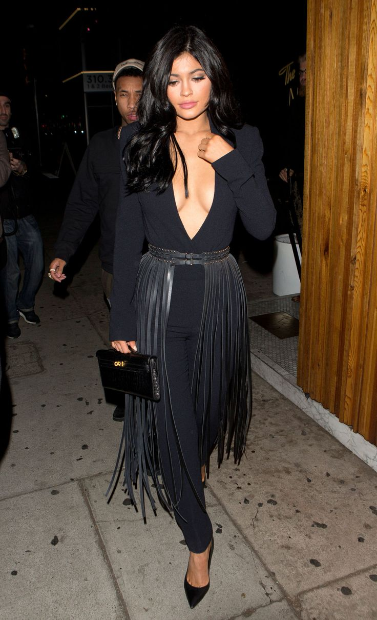 Kylie Jenner, a woman who has worn giant feather skirts in the desert, tried another statement piece in the streets of West Hollywood last night. She left the Nice Guy club in a can't-get-any-lower v-neck jumpsuit, cinched at the waist with a black, 1,400 € ($1,509) YVY fringe belt. The thing was so long, it doubled as a couture hula skirt.