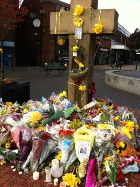 Flowers and lovely written tributes at the ancient stone cross in the Eccles town centre for assassinated aid worker and cab driver Alan Henning, Manchester, England, United Kingdom, 2014, photograph by Edwina Wolstencroft. Henning would save his taxi driving wages for the entire year and, along with his wife, would use whatever they could allot to help relieve the suffering of the poor and displaced all over the world.
