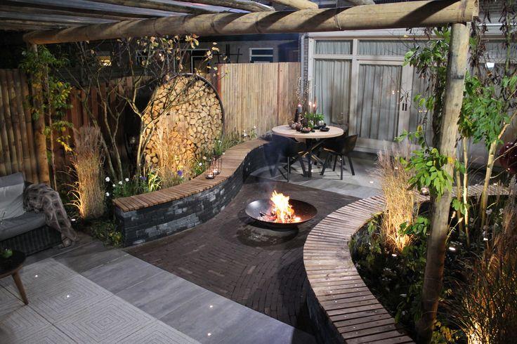 Romantische tuin met verschillende zitplekken, een kronkelende tuinbank en een handige haardopslag