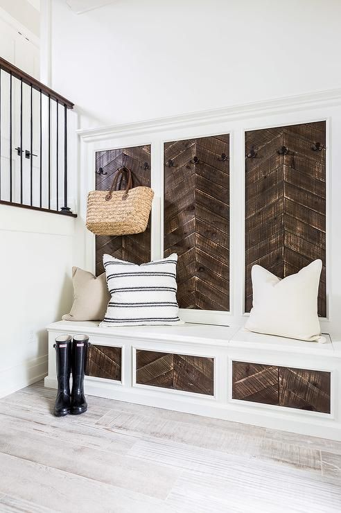 Symphony Showhouse - Country mudroom boasts a mudroom bench and backsplash fitted with inset wood herringbone panels lined with iron coat hooks.
