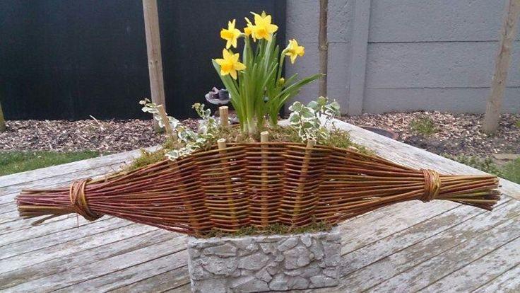 Geweven takken compositie gevuld met voorjaarsplantjes